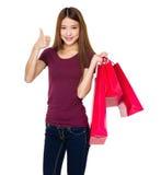 Tenuta della donna con il sacchetto della spesa ed il pollice su Immagini Stock Libere da Diritti