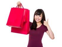 Tenuta della donna con il sacchetto della spesa ed il pollice su Fotografia Stock