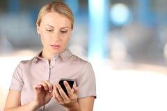 Tenuta della donna di affari e per mezzo dello Smart Phone mobile Immagini Stock