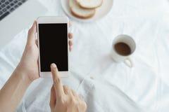 Tenuta della donna lavoratrice delle mani e Smart Phone usando sul fondo dello scrittorio Sullo scrittorio abbia il caffè, i pani fotografie stock libere da diritti
