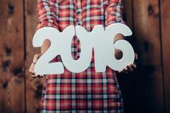 Tenuta della donna nei numeri del nuovo anno 2016 delle mani Fotografia Stock