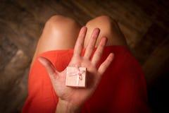 Tenuta della donna in sua mano un contenitore di regalo rosa molto piccolo sopra il suo K Immagine Stock