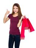 Tenuta della giovane donna con il sacchetto della spesa ed il pollice su Immagini Stock Libere da Diritti