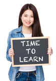 Tenuta della giovane donna con la lavagna che mostra frase di tempo di imparare immagine stock libera da diritti