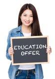 Tenuta della giovane donna con la lavagna che mostra offerta di istruzione Fotografie Stock