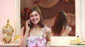 Tenuta della giovane donna ed usando telefono cellulare attraenti a casa video d archivio