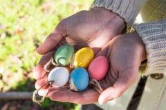 Tenuta della giovane donna in uova di Pasqua variopinte decorative delle mani su cordicella, all'aperto, erba verde Immagini Stock