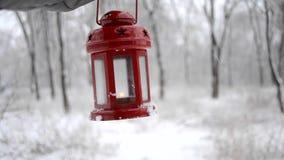 Tenuta della lanterna rossa della candela nella foresta di inverno stock footage