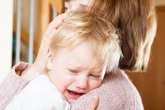 Tenuta della mamma che grida bambino fotografia stock libera da diritti
