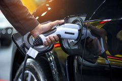 Tenuta della mano che carica l'accumulatore per di automobile elettrica fotografie stock