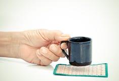 Tenuta della mano dell'uomo anziano con la tazza nera sulla tavola bianca Fotografia Stock