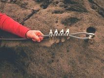 Tenuta della mano dello scalatore sulla corda torta acciaio all'occhio del bullone d'acciaio ancorato in roccia Fotografie Stock