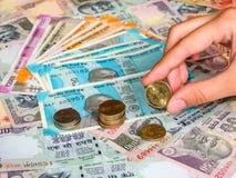 Tenuta della mano una moneta da 5 rupie sopra vecchie e nuove le note indiane delle rupie, primo piano immagini stock