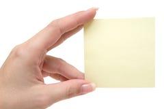 Tenuta della nota gialla fotografie stock