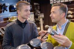 Tenuta della persona con il club di golf della mano nel negozio di golf Immagine Stock Libera da Diritti