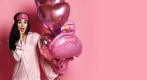 Tenuta della ragazza di Valentine Beauty rossa e aerostati rosa che ridono sul fondo rosa che celebra giorno di biglietti di S. V fotografia stock libera da diritti
