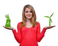 Tenuta della ragazza nelle mani generatore eolico e nell'icona della centrale atomica Fotografia Stock