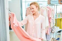 Tenuta della ragazza in un negozio di vestiti Fotografia Stock Libera da Diritti
