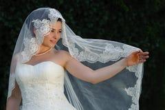 Tenuta della sposa aperta il suo velo nuziale con il dito Fotografie Stock