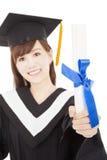 Tenuta della studentessa del giovane laureato e diploma di rappresentazione Immagine Stock Libera da Diritti