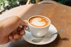 Tenuta della tazza di caffè calda sulla tavola Fotografia Stock Libera da Diritti
