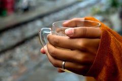 Tenuta della tazza di t? dal pullover delle rotaie che riguarda le mani da un terzo immagine stock libera da diritti