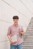 Tenuta dello studente con il computer portatile dentro il buildi della città universitaria della scuola Immagine Stock