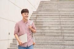 Tenuta dello studente maschio con il computer portatile al campus universitario Fotografia Stock