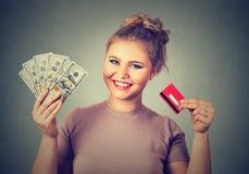 Tenuta di acquisto della donna che mostra le fatture delle banconote del dollaro della carta di credito e dei contanti Immagine Stock