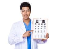 Tenuta di medico dell'ottico con il eyechart fotografia stock