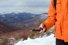 Tenuta di viaggiatore con zaino e sacco a pelo in sua mano GPS Fotografia Stock