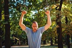 Tenuta dura dell'uomo sugli anelli di ginnastica Immagine Stock Libera da Diritti