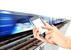 Tenuta e touch screen della mano della donna sullo smartphone o sul telefono cellulare sopra Immagine Stock