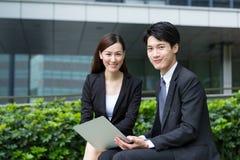 Tenuta felice dell'uomo e della donna di affari con il computer portatile Fotografie Stock