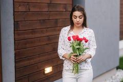 Tenuta felice della donna un mazzo dei fiori l'ottavo marzo fotografie stock