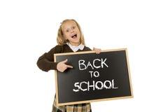 Tenuta felice sorridente della scolara e lavagna di rappresentazione piccola con testo di nuovo alla scuola Immagini Stock