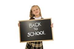 Tenuta felice sorridente della scolara e lavagna di rappresentazione piccola con testo di nuovo alla scuola Immagini Stock Libere da Diritti