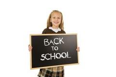 Tenuta felice sorridente della scolara e lavagna di rappresentazione piccola con testo di nuovo alla scuola Immagine Stock Libera da Diritti