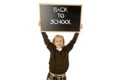 Tenuta felice sorridente della scolara e lavagna di rappresentazione piccola con testo di nuovo alla scuola Fotografia Stock