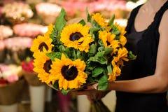 Tenuta femminile del fiorista del negozio di fiore dei girasoli del mazzo Immagine Stock Libera da Diritti