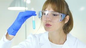 Tenuta femminile dello scienziato ed esaminare soluzione blu in boccetta in laboratorio video d archivio