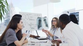 Tenuta femminile di medico in lastra radioscopica delle mani durante la conferenza in clinica Medici professionisti di multi grup video d archivio