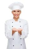Tenuta femminile sorridente del cuoco unico qualcosa sulle mani Fotografia Stock