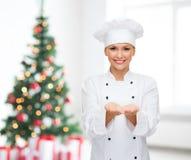 Tenuta femminile sorridente del cuoco unico qualcosa sulle mani Immagini Stock