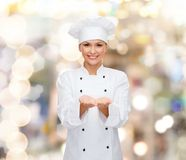 Tenuta femminile sorridente del cuoco unico qualcosa sulle mani Immagine Stock