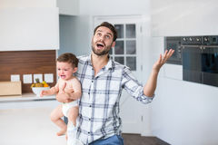 Tenuta frustrata del padre che grida neonato in cucina Fotografia Stock