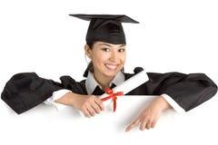 Tenuta laureata sorridente della femmina un segno con il diploma Immagini Stock Libere da Diritti