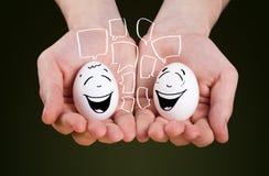 La tenuta maschio della tenuta della mano eggs con i fronti sorridente Fotografia Stock