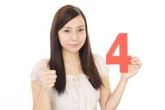 Tenuta numero quattro della donna fotografie stock