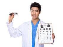 Tenuta ottica di medico con il eyechart e il glassesa immagine stock libera da diritti